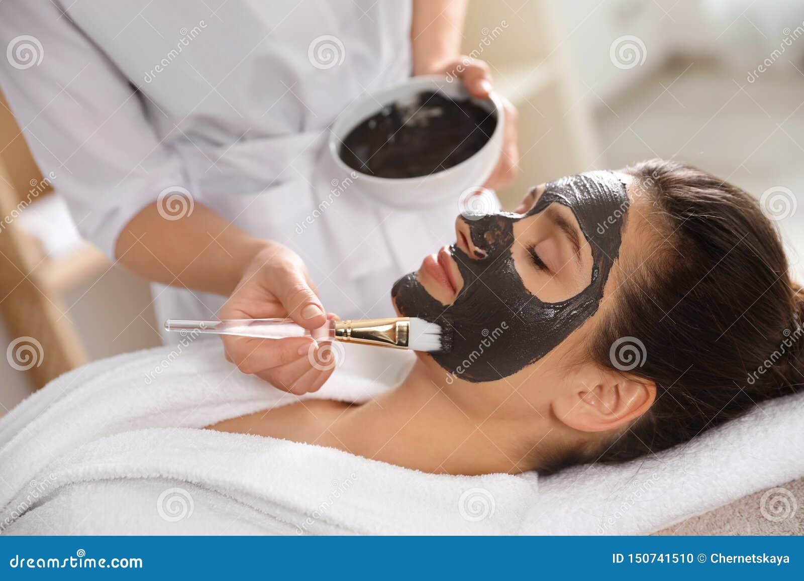 Cosmetologist die zwart masker op het gezicht van de vrouw toepassen