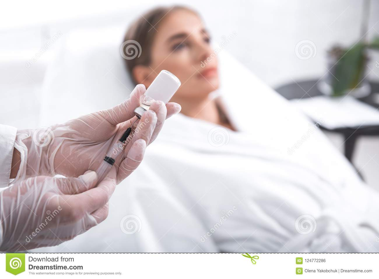Cosmetologist filling syringe while young lady lying on daybed