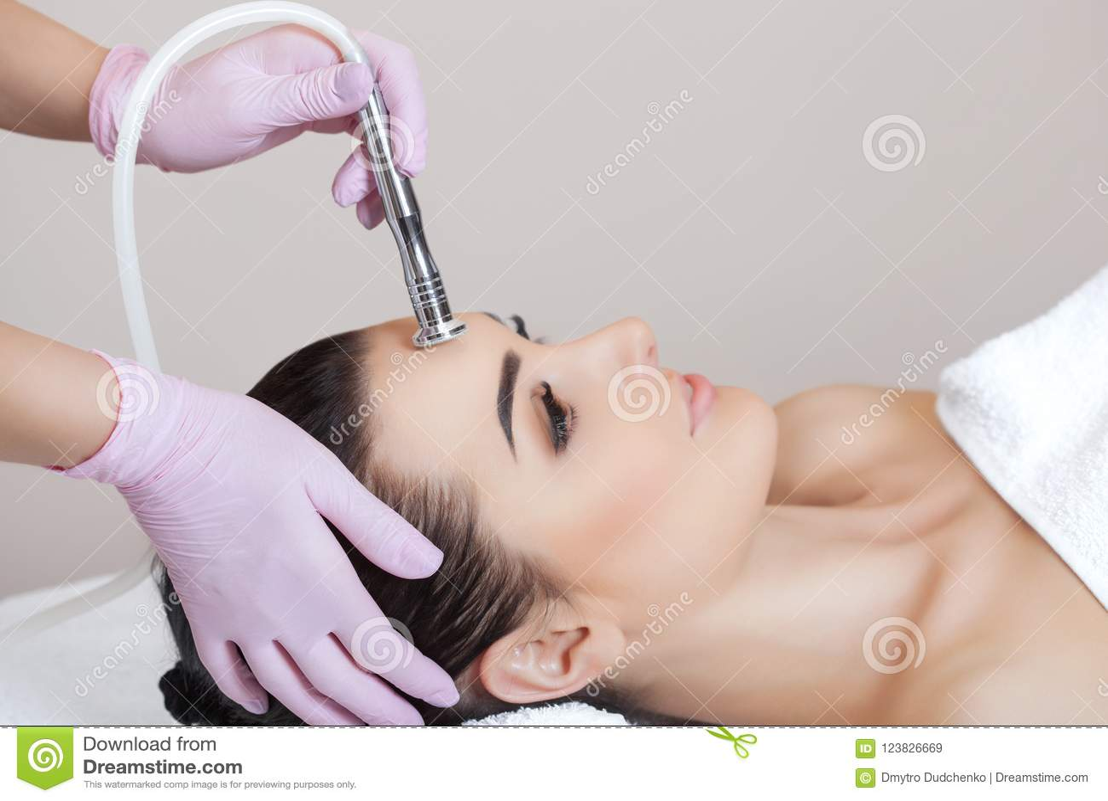 Cosmetologist maakt de procedure Microdermabrasion van de gezichtshuid van een mooie, jonge vrouw in een schoonheidssalon