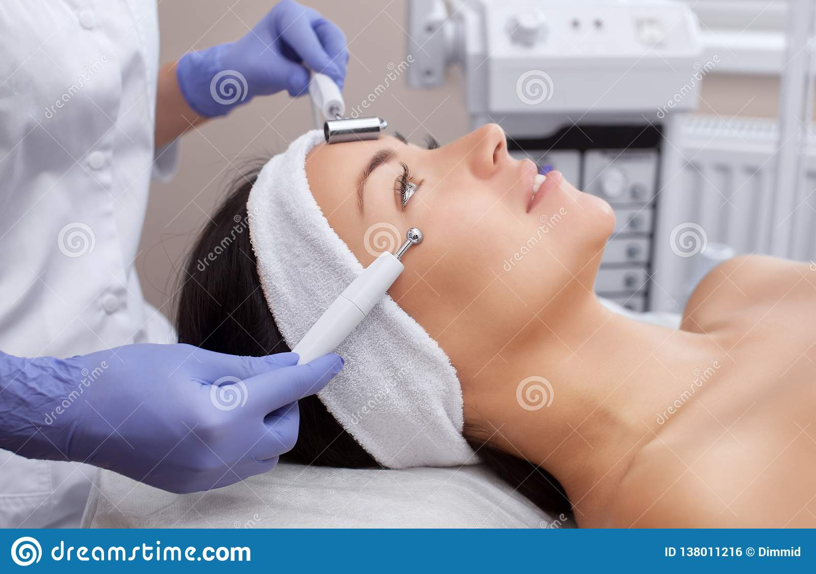 The cosmetologist makes the apparatus a procedure of Microcurrent therapy of a beautiful, young woman in a beauty salon