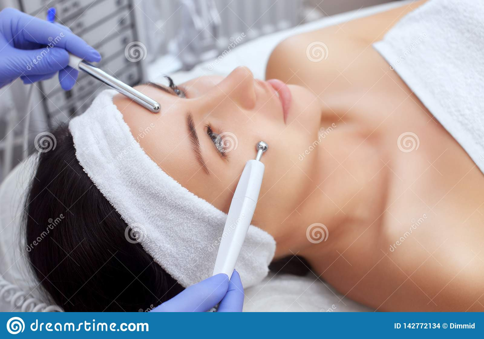 The cosmetologist makes the apparatus a procedure of Microcurrent therapy of a beautiful, young woman in a beauty salon.