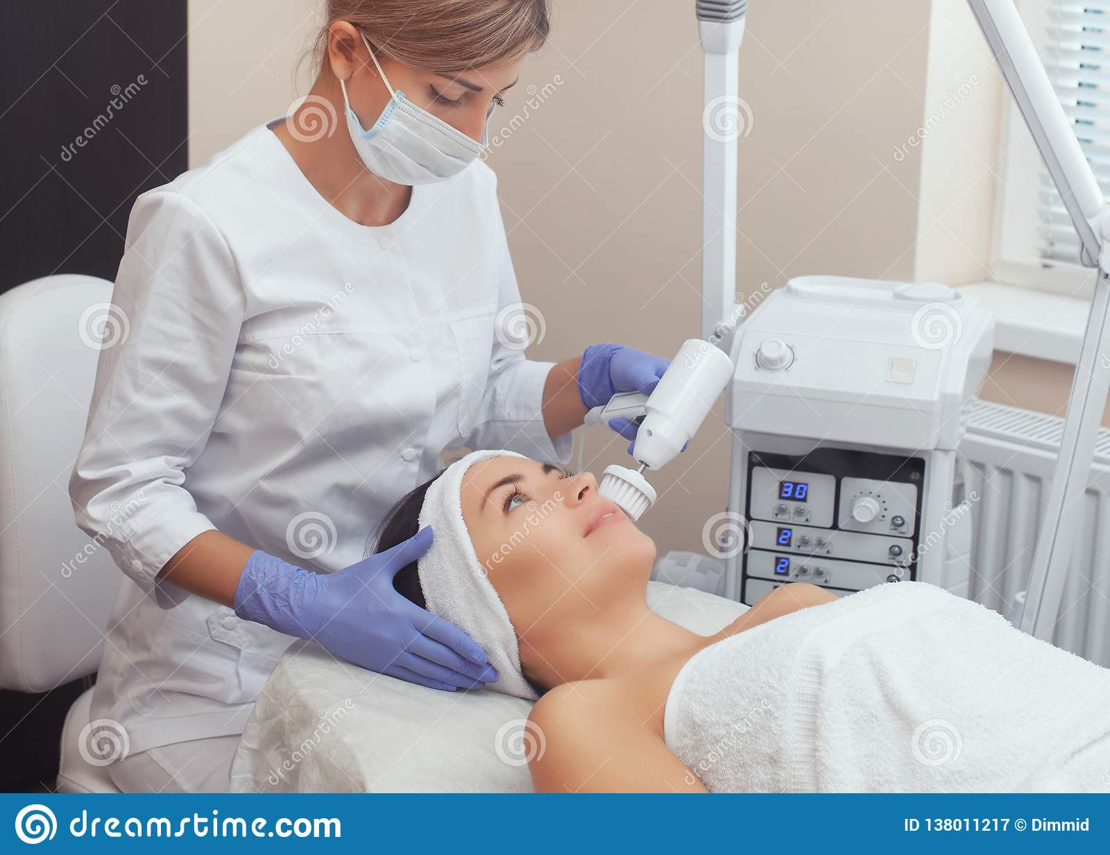 The cosmetologist makes the Hardware face cleaning procedure with a soft rotating brush of a beautiful, young woman in a beauty