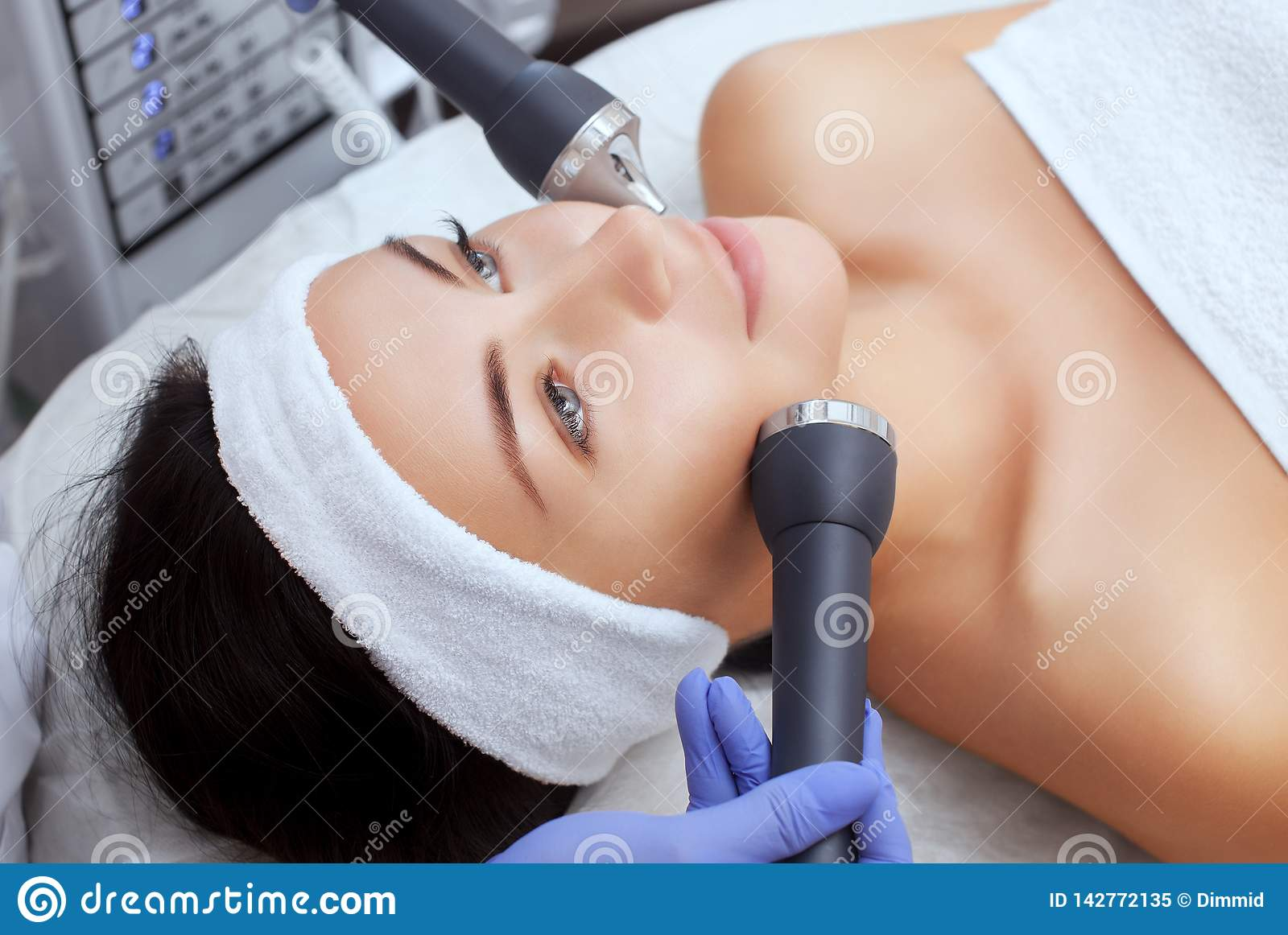 The cosmetologist makes the procedure an ultrasonic cleaning of the facial skin of a beautiful, young woman in a beauty salon