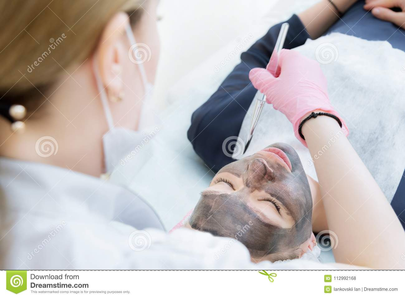 The cosmetologist in pink gloves with a brush applies a carbon mask for peeling on the face of a young girl in a