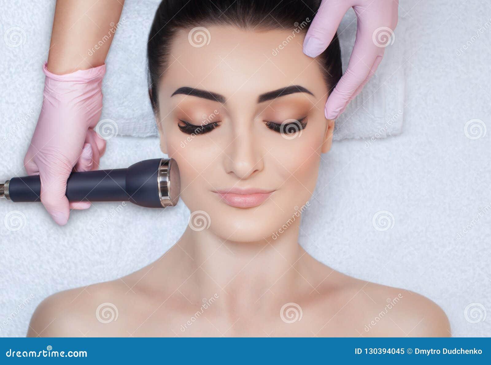 Cosmetologist robi procedurze ultrasonic cleaning twarzowa skóra piękny, młoda kobieta w piękno salonie
