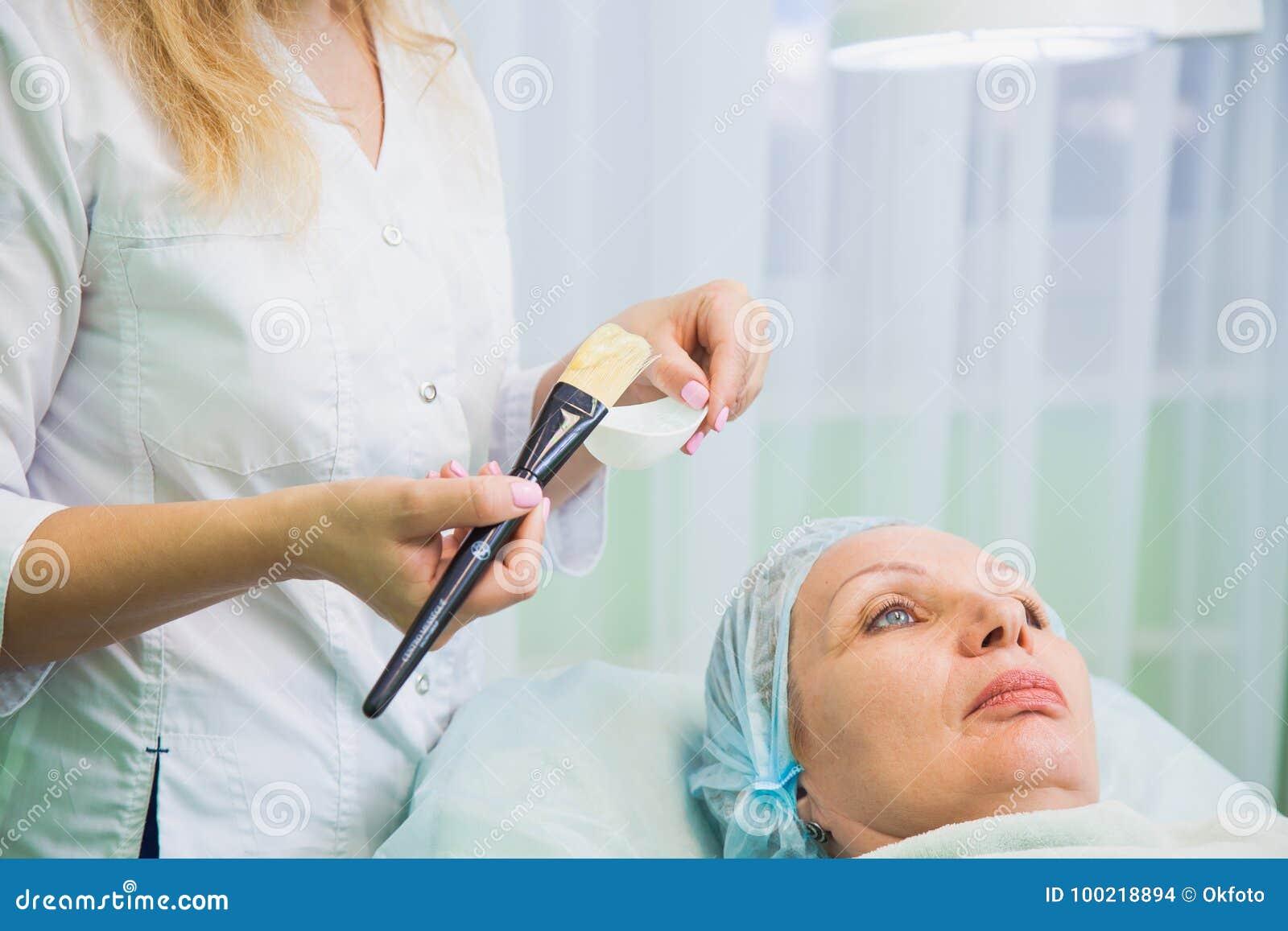 Cosmetologo che applica maschera sul fronte senior della donna