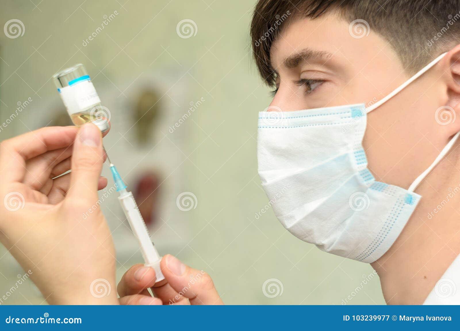 Cosmetologo maschio con la maschera medica sul fronte