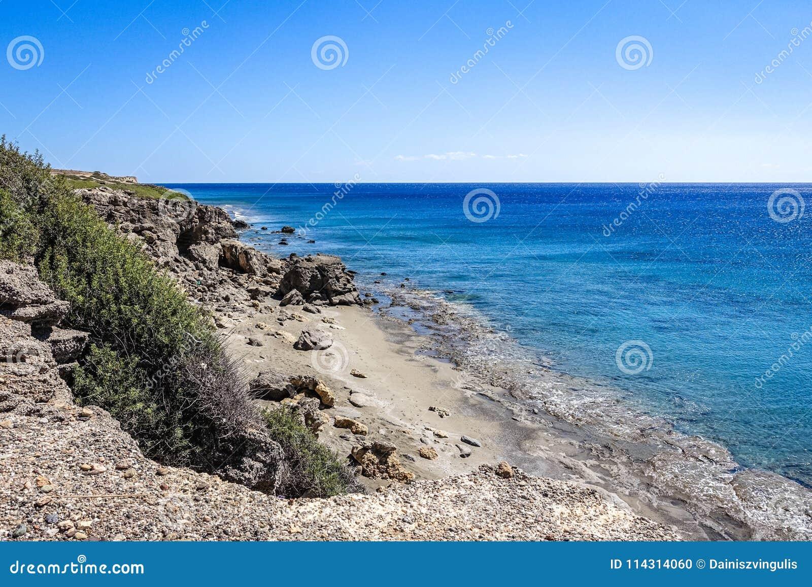 A costa é rochosa, uma angra arenosa pequena é visível