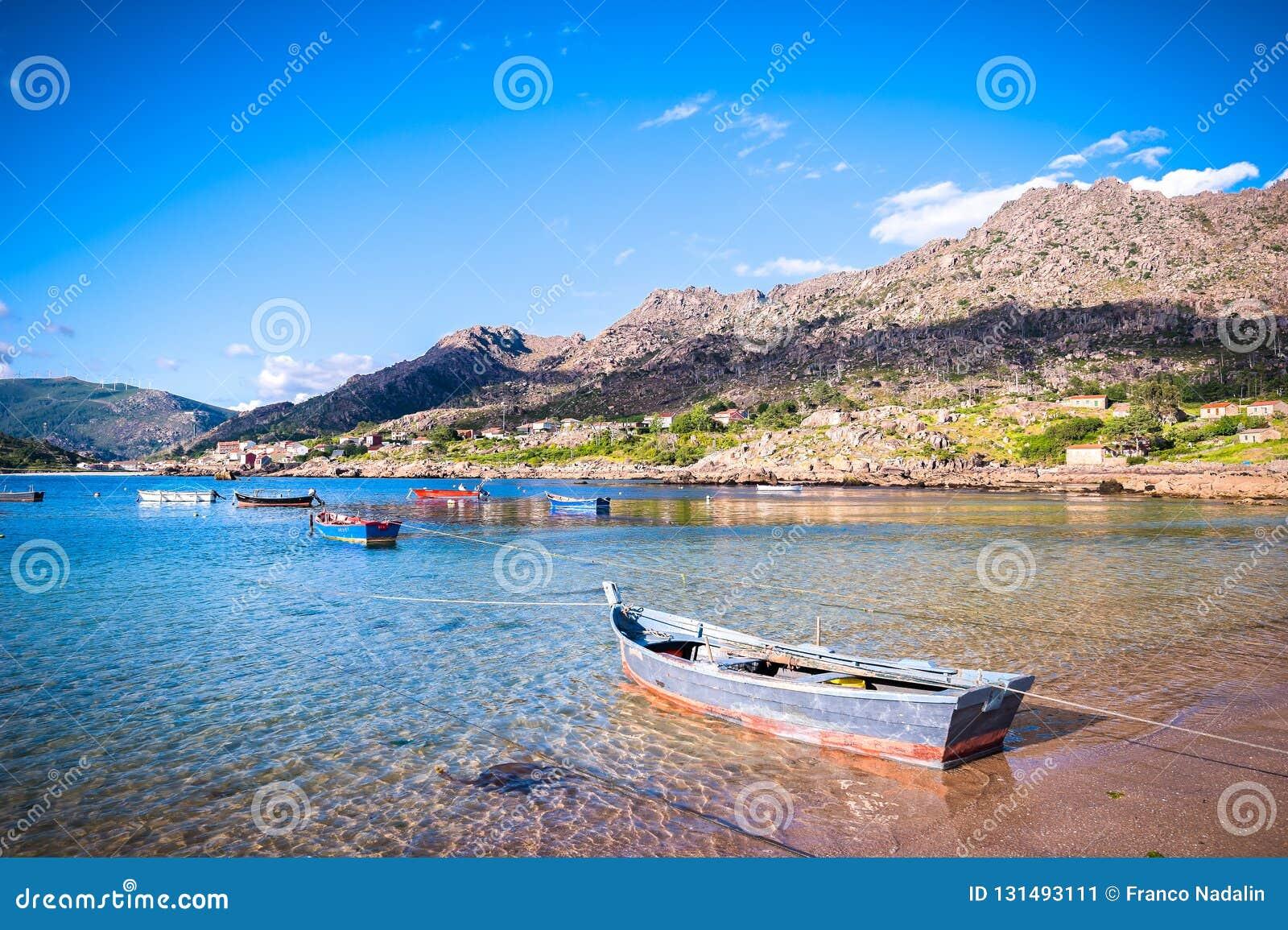 Costa atlántica de la belleza con los barcos de pesca, la playa, el océano, el pueblo, las montañas y el cielo con las nubes Gali