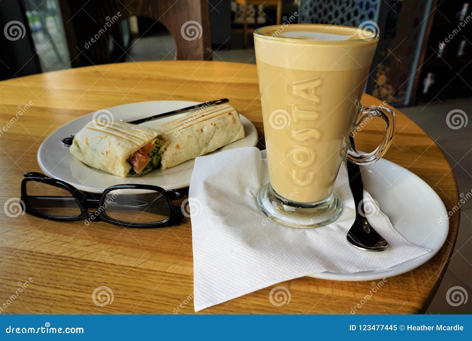 Costa brand American coffee latte, breakfast sandwich and reading glasses