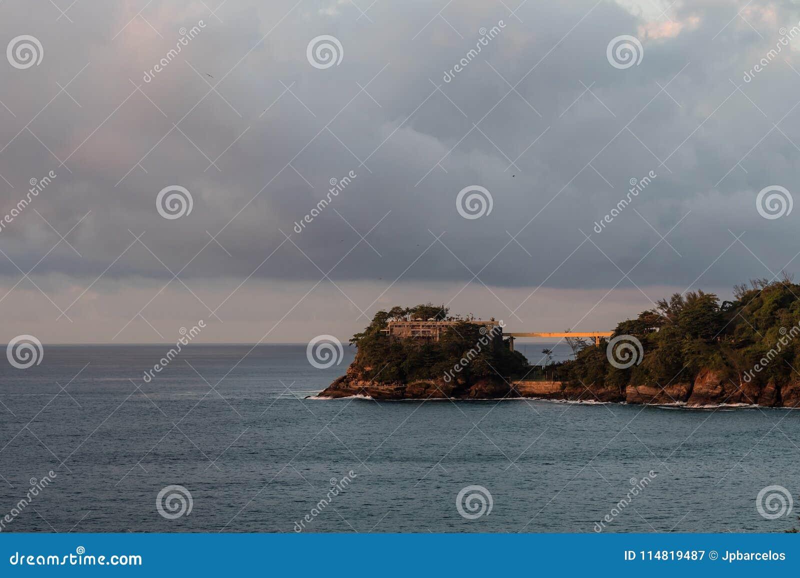 Costa Brava ö som ses från den Joa huvudvägen under soluppgång, orange ljus i molnig morgon, Rio de Janeiro, Brasilien