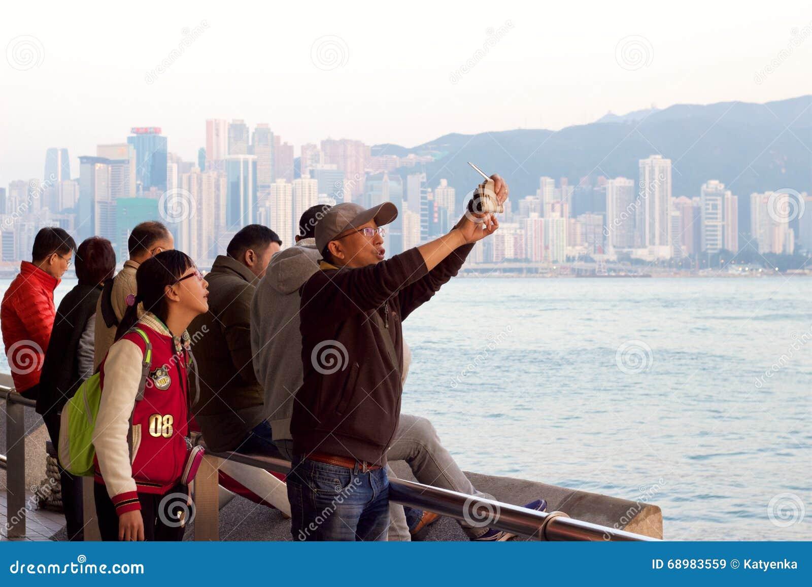 Costa de Hong Kong: Puesta del sol de fotografía de la gente en la oscuridad
