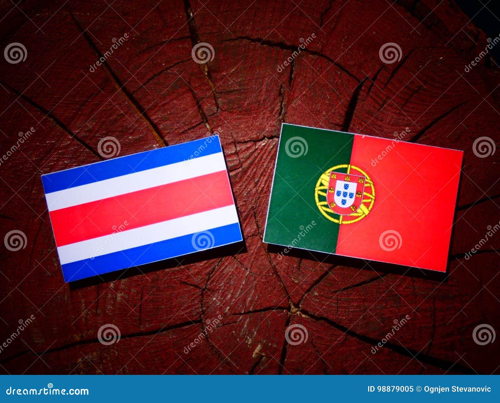 Costa Rican-vlag met Portugese vlag op een geïsoleerde boomstomp