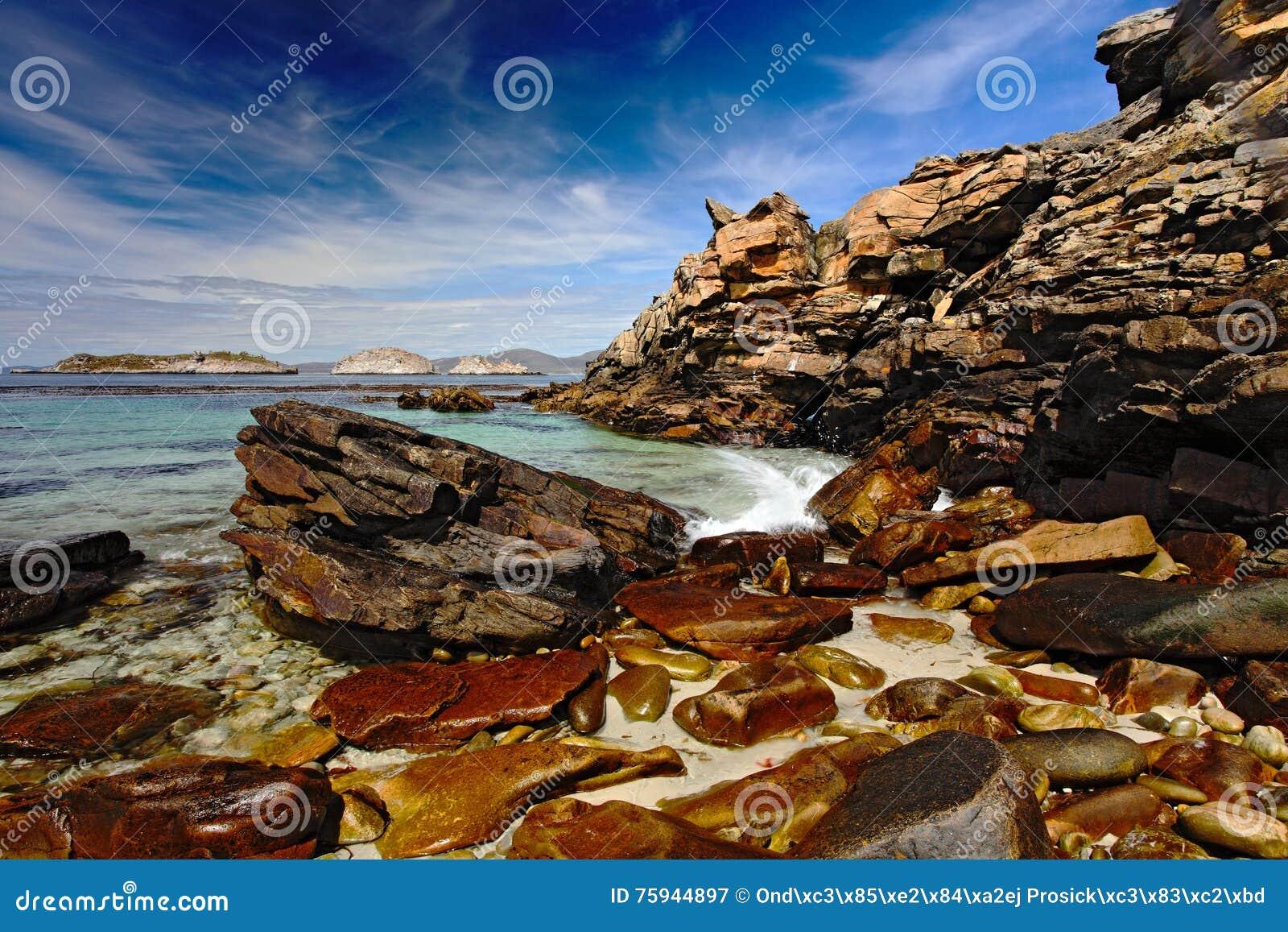 Costa rochosa com obscuridade - céu azul com nuvens brancas Mar com obscuridade - céu azul Pedras no mar Costa do oceano com prai
