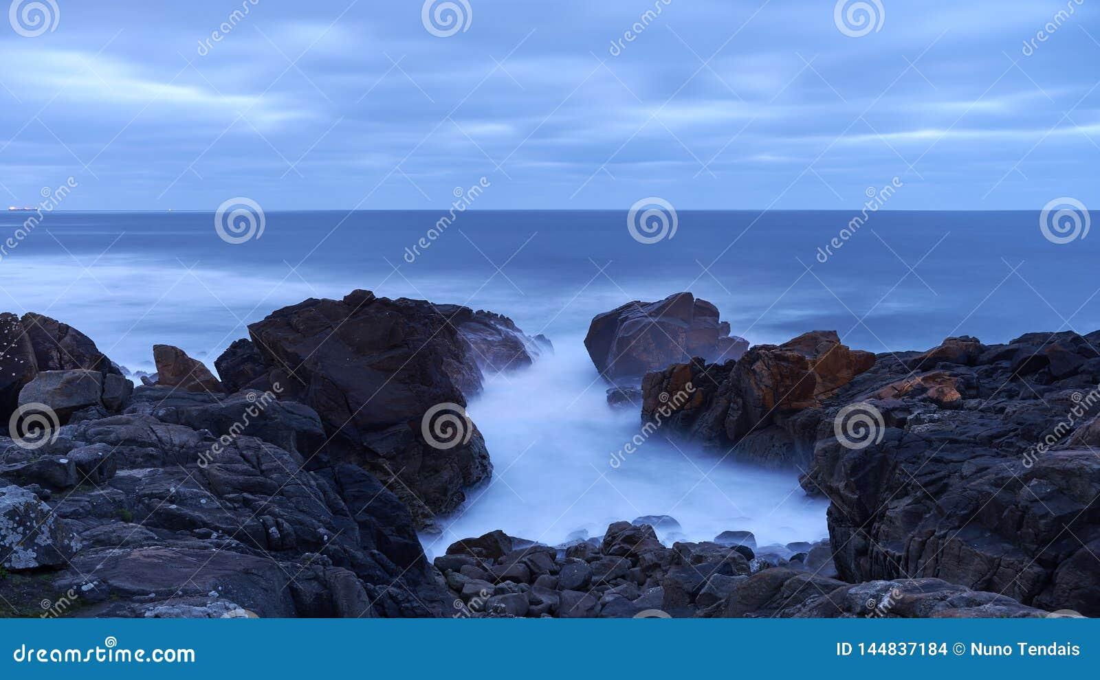 Coste rocoso negro en la hora azul