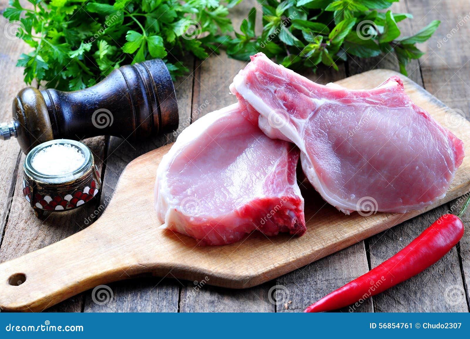 Costeleta de carne de porco crua no osso com salsa, hortelã, pimenta e sal do mar