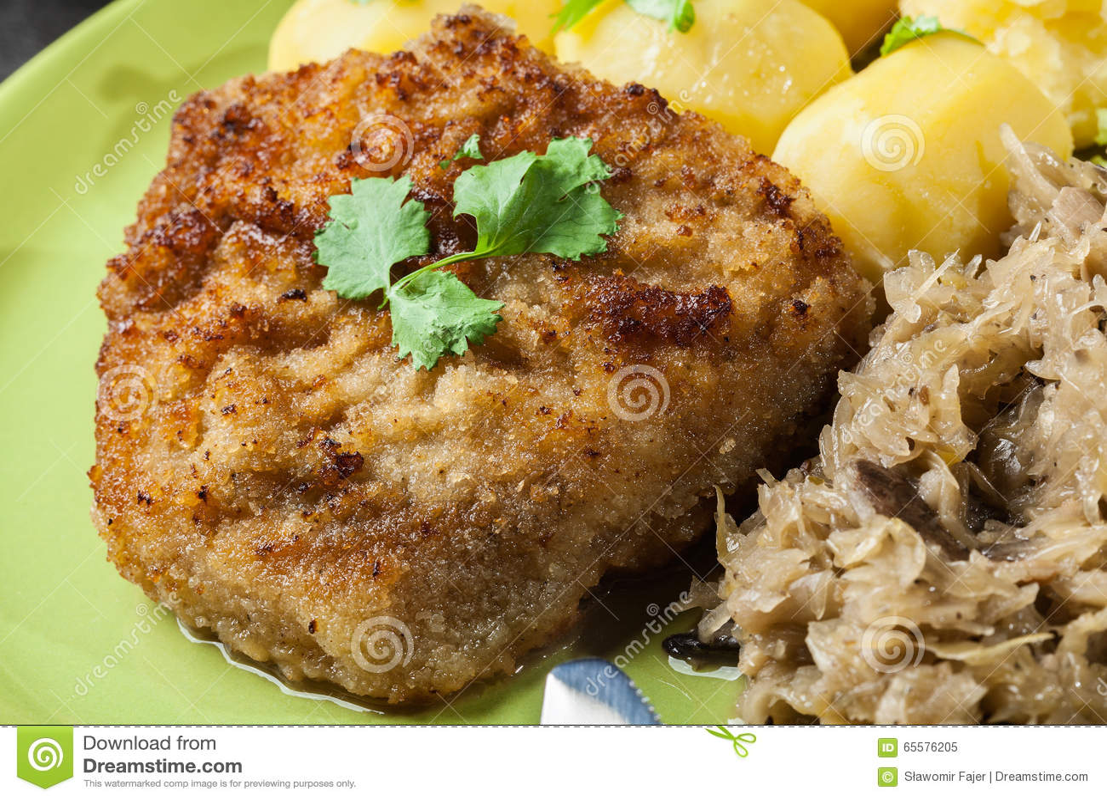 A costeleta de carneiro fritada da carne de porco serviu com batatas fervidas e fritou sauer