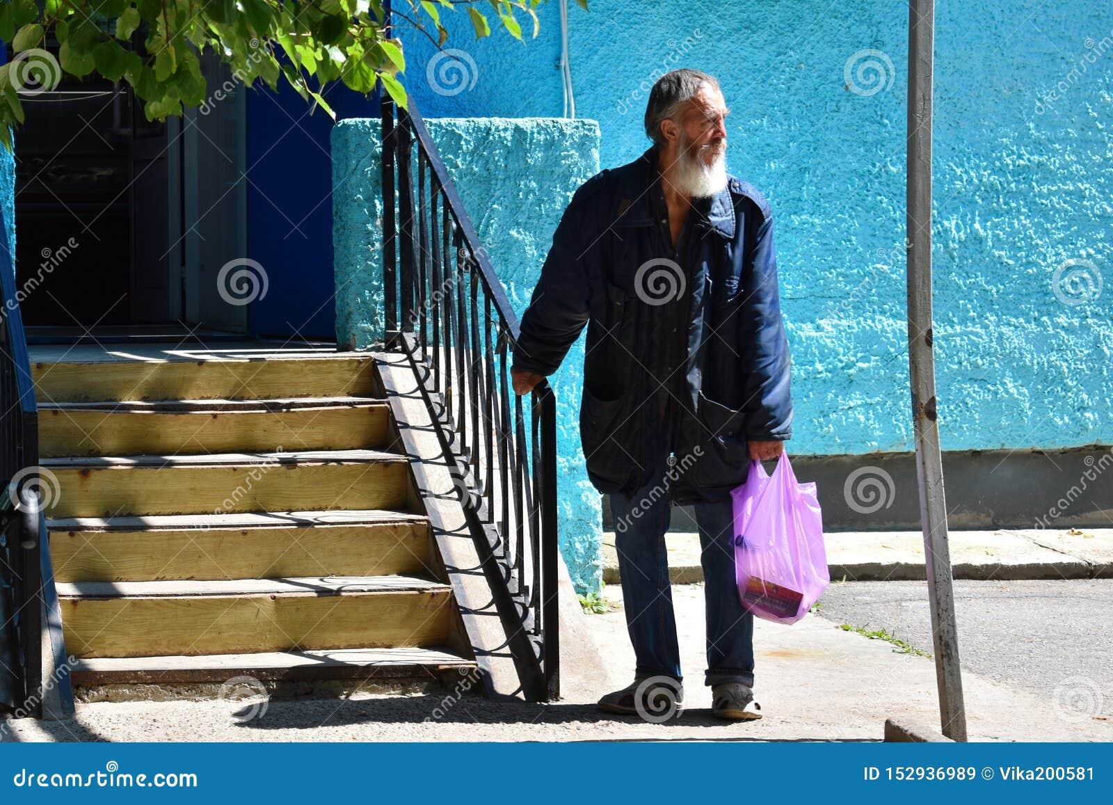 Costes desempleados homless pobres del viejo hombre en una entrada a hacer compras