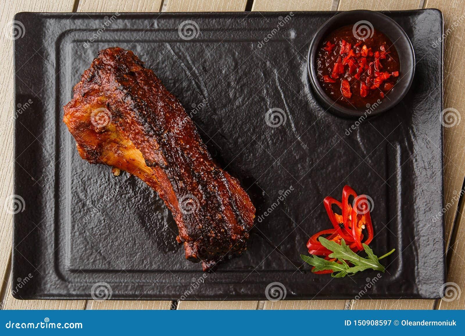 Costillas calientes asado a la parrilla y de la barbacoa de cerdo con pimienta de chiles calientes y salsa caliente en fondo de p
