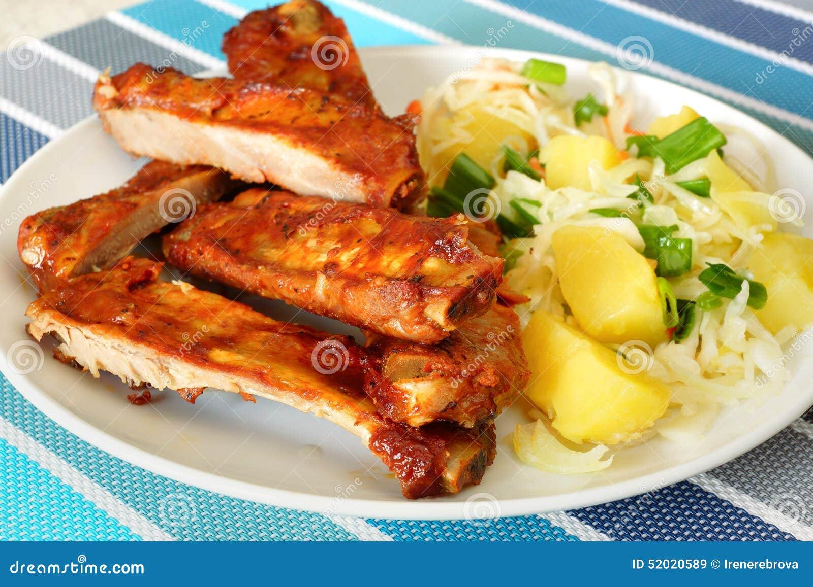Costillas de cerdo cocidas con la ensalada de patata
