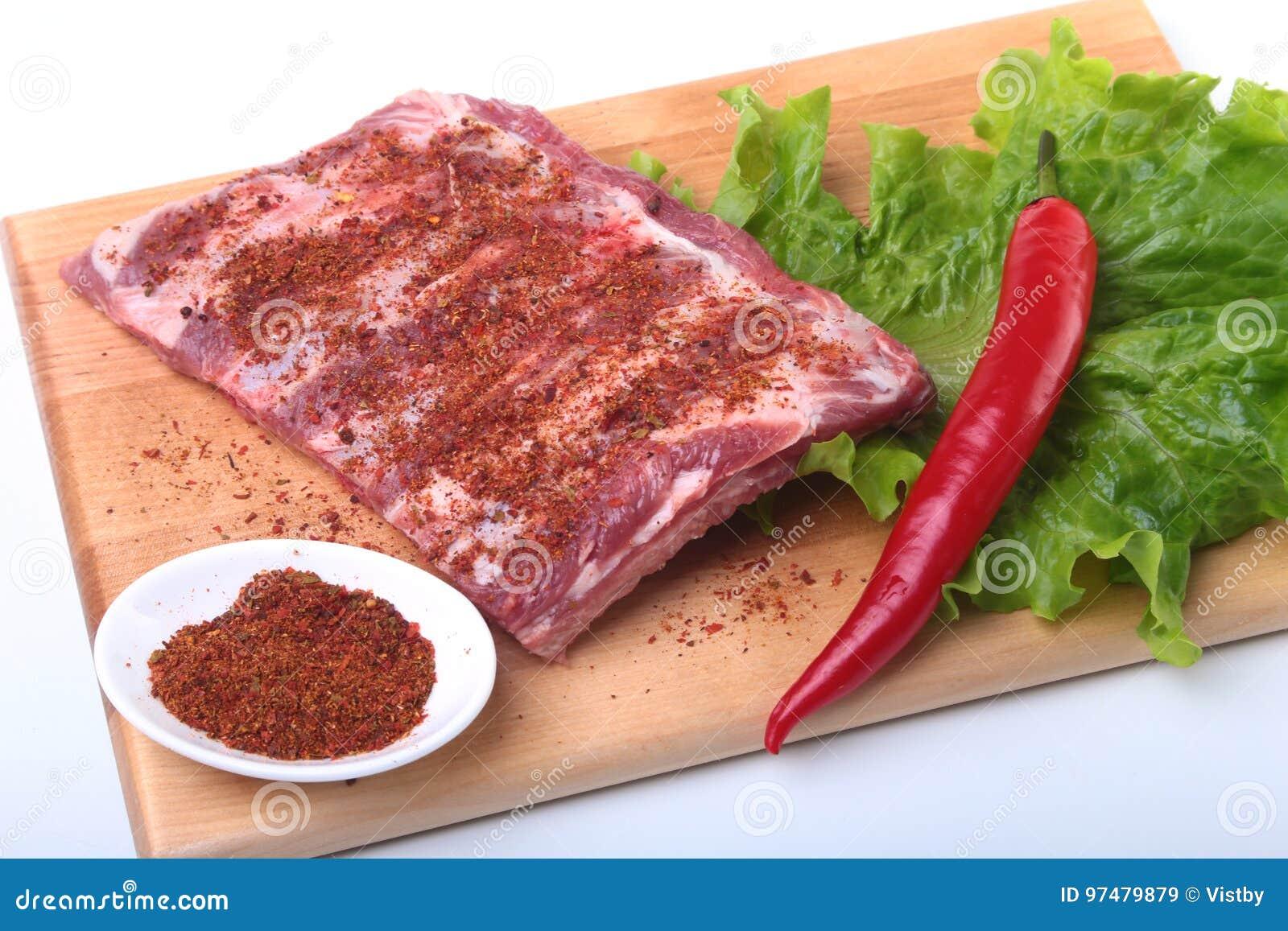 Costole di carne di maiale crude con le erbe e le spezie sul bordo di legno Aspetti per cucinare