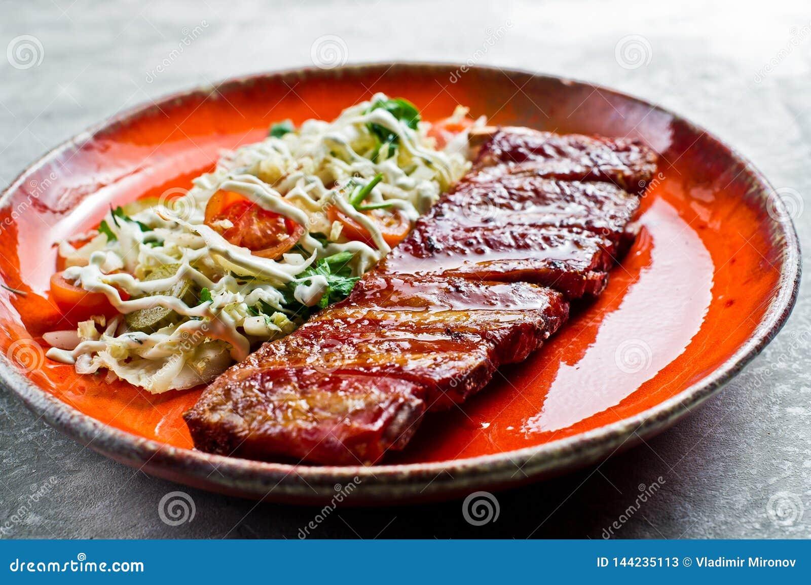 Costole di carne di maiale americane tradizionali del barbecue con un piatto laterale di insalata verde Fondo grigio