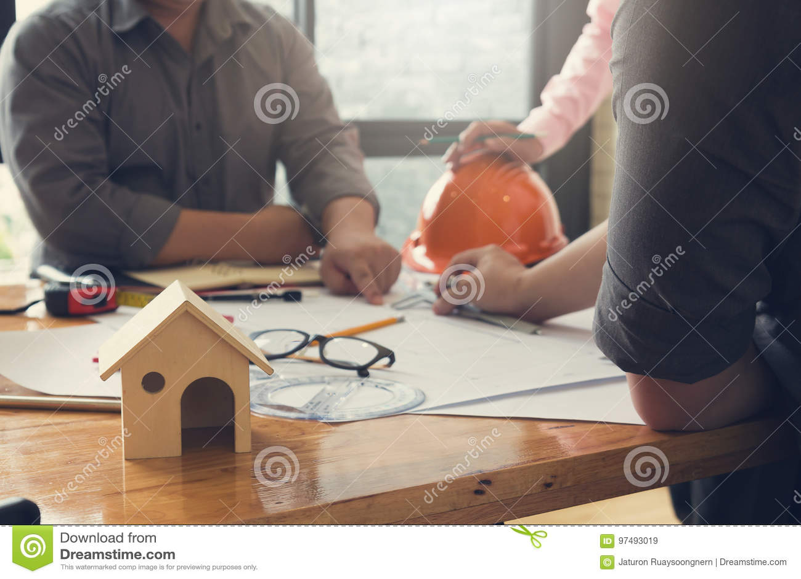 Costruisca il gruppo dell ufficio di Architects che lavora e che discute la pianta della casa con i modelli ed il modello della c