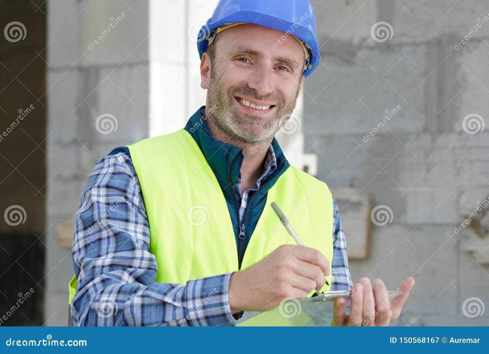 Costruttore maschio felice in casco con la lavagna per appunti