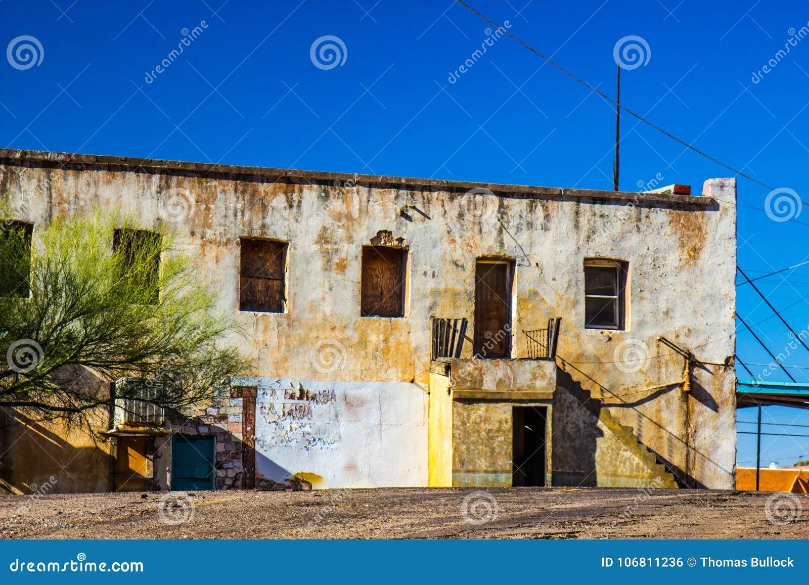 Costruzione abbandonata dello stucco con imbarcato su Windows & sulle porte
