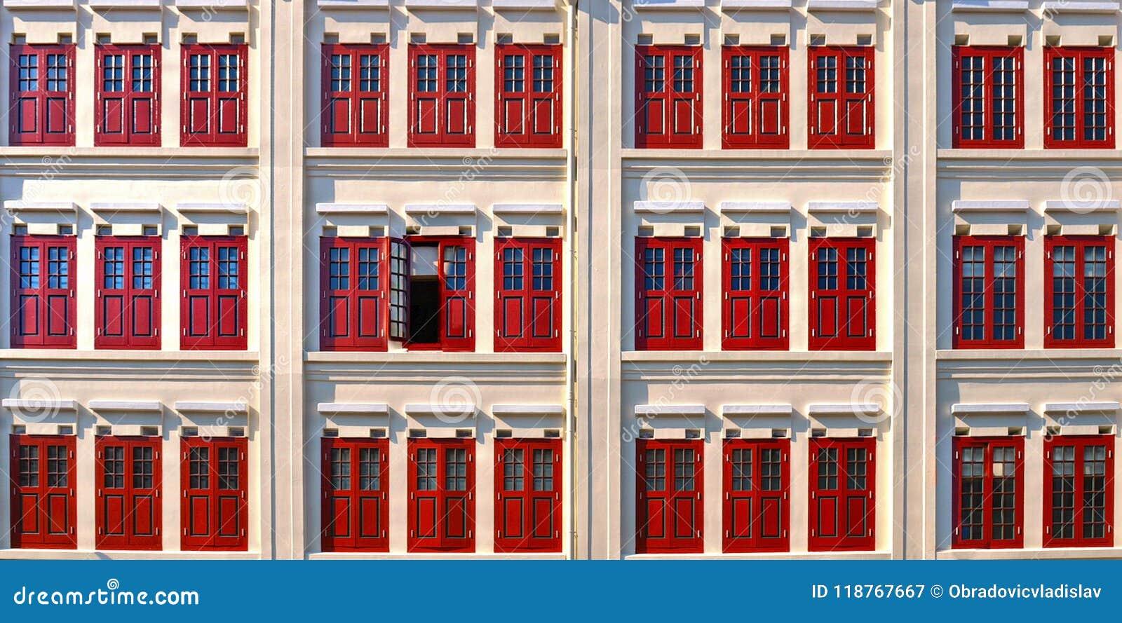 Costruzione bianca e finestre rosse nelle costruzioni coloniali classiche di architettura nella città della porcellana di Singapo