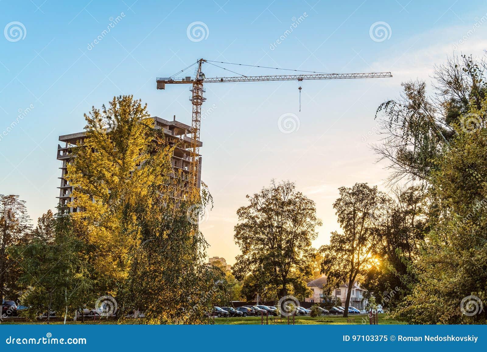Costruzione di alloggi urbana Gru a torre con una costruzione multipiana in costruzione nella sera fra gli alberi di autunno