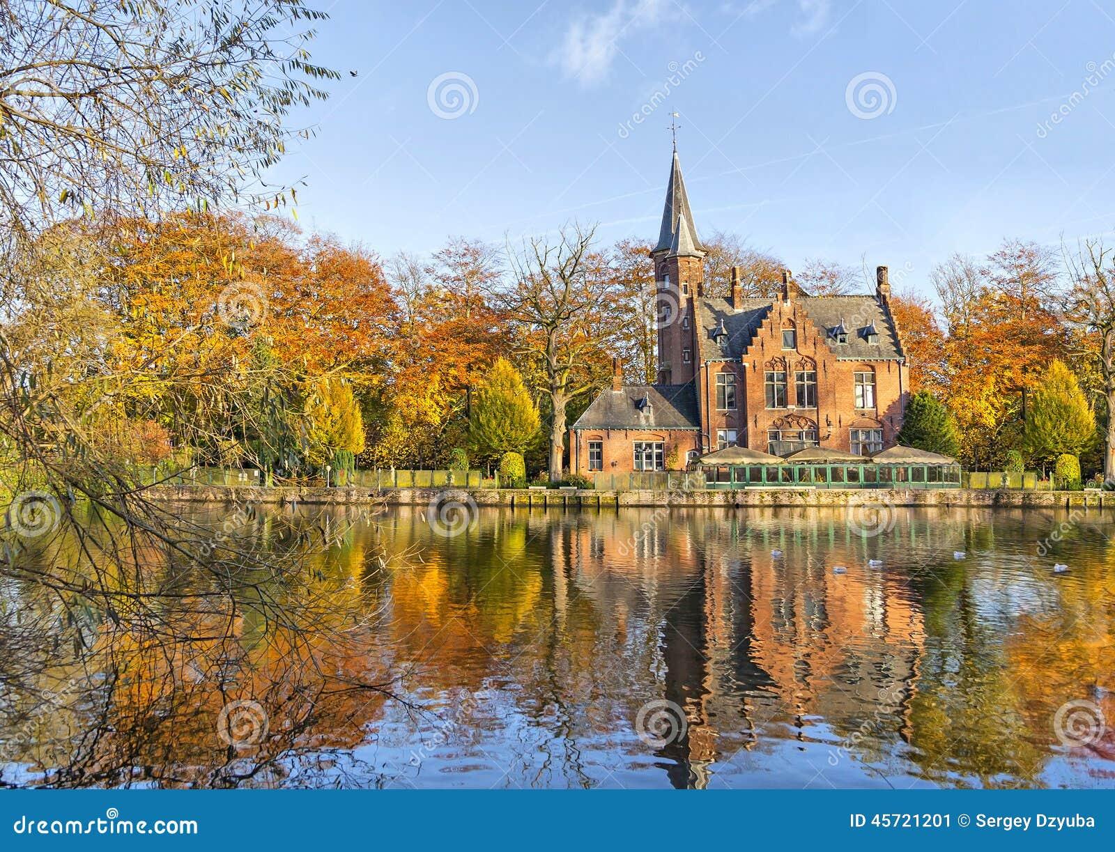 Costruzione fiamminga di stile che riflette nel lago Minnewater, Bruges