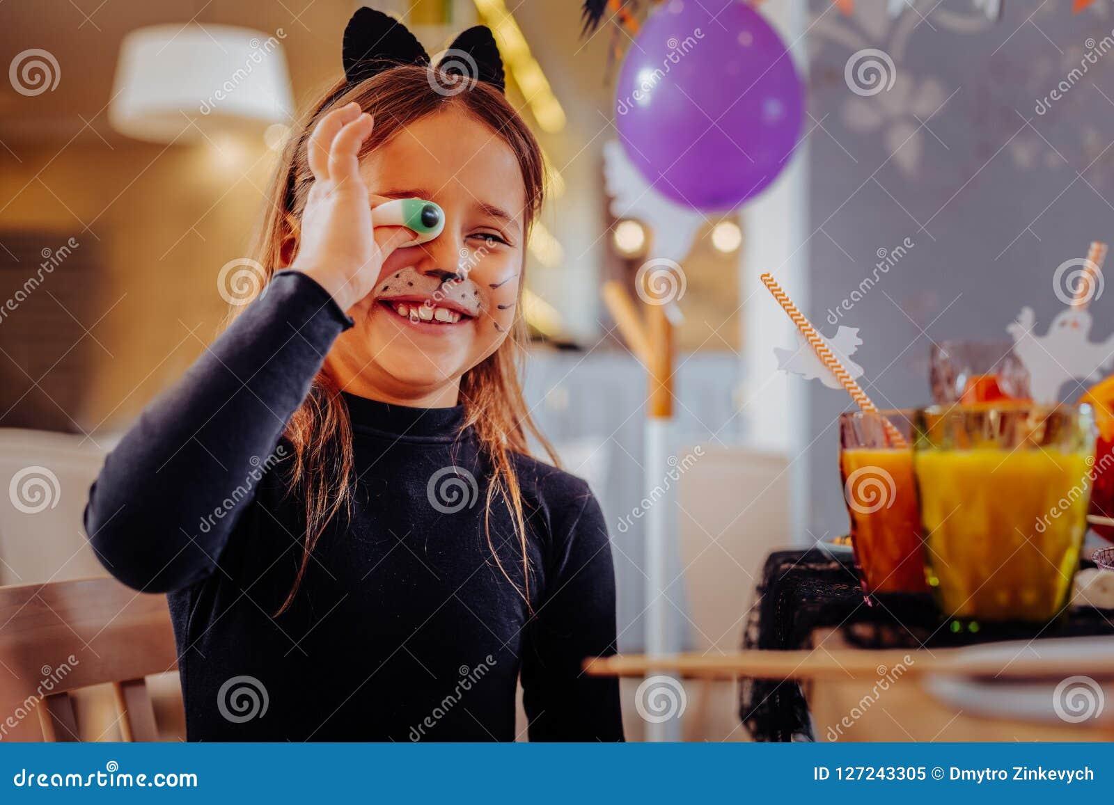 Costume de port de chat de fille aux cheveux foncés gaie souriant largement tenant l oeil gommeux