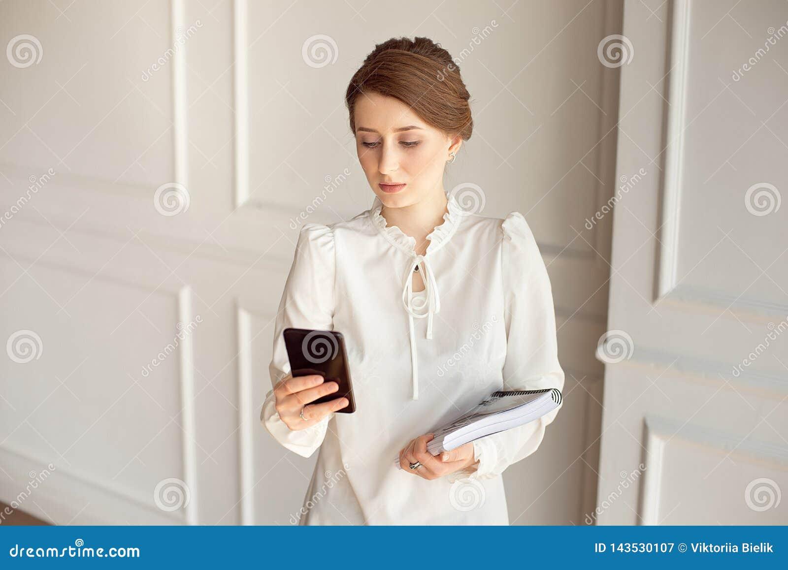 Costume de port de femme d affaires de photo, regardant le smartphone et tenant des documents dans des mains