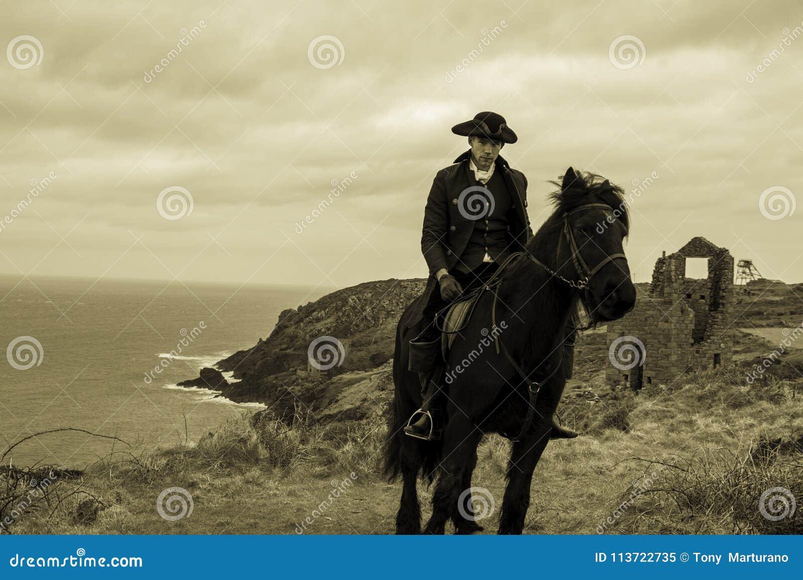 Costume del XVIII secolo bello di Rider Regency Poldark del cavallo maschio con le rovine della miniera di latta e l Oceano Atlan
