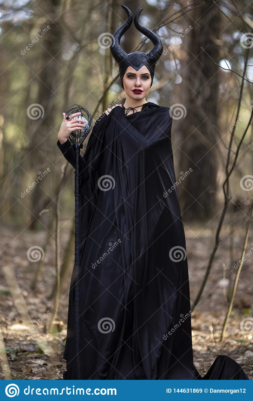 Costume Drama. Marvellous and Magical Maleficent Woman with Horns Posing in Spring Empty Forest with Crook