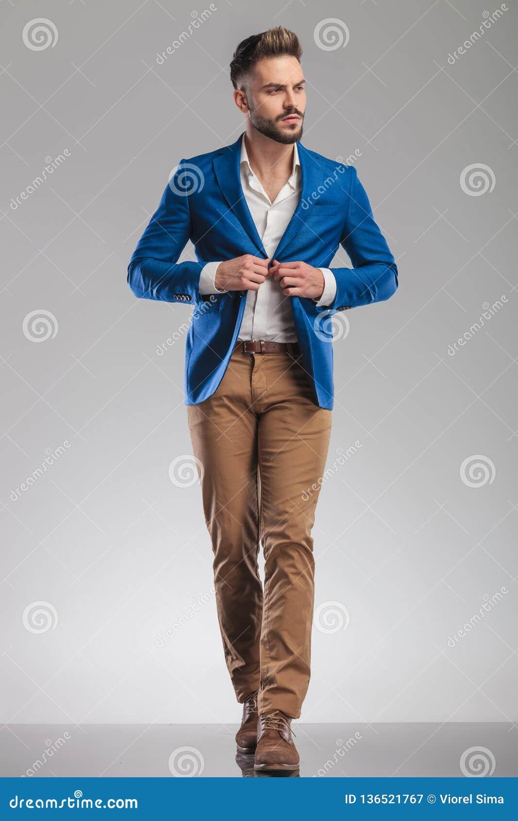 Costume occasionnel futé curieux de boutons d homme tout en marchant en avant