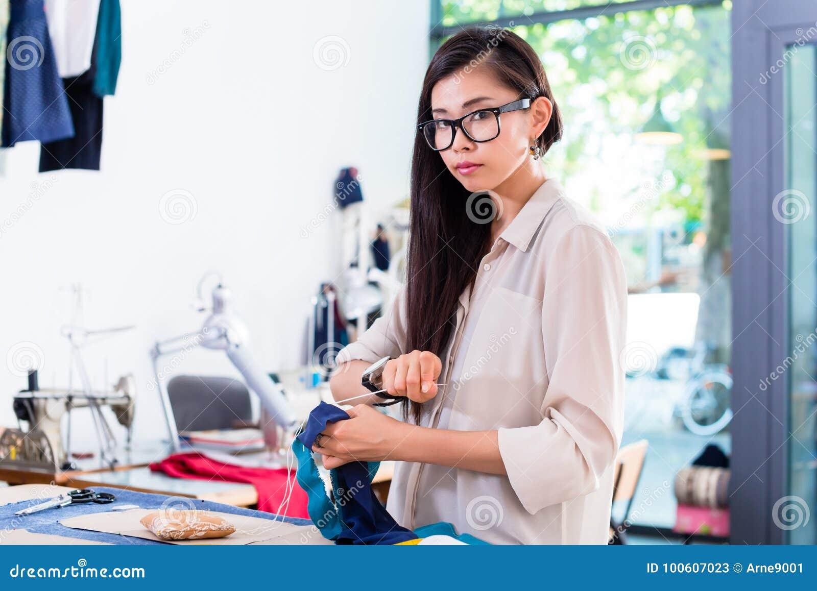 Costura asiática da mulher do desenhador de moda em sua oficina
