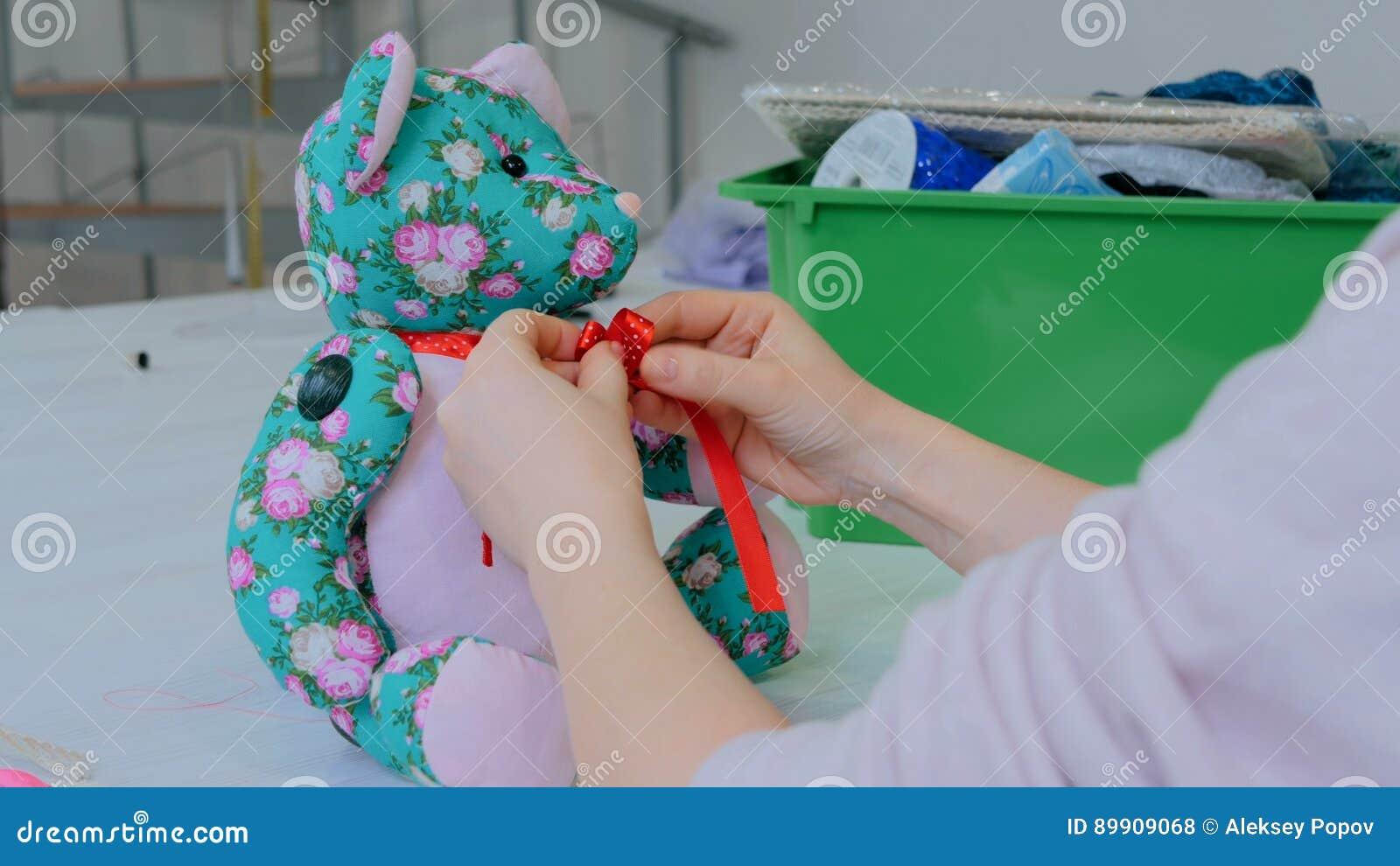 Costure a mulher, toymaker que amarra a curva no pescoço do urso de peluche