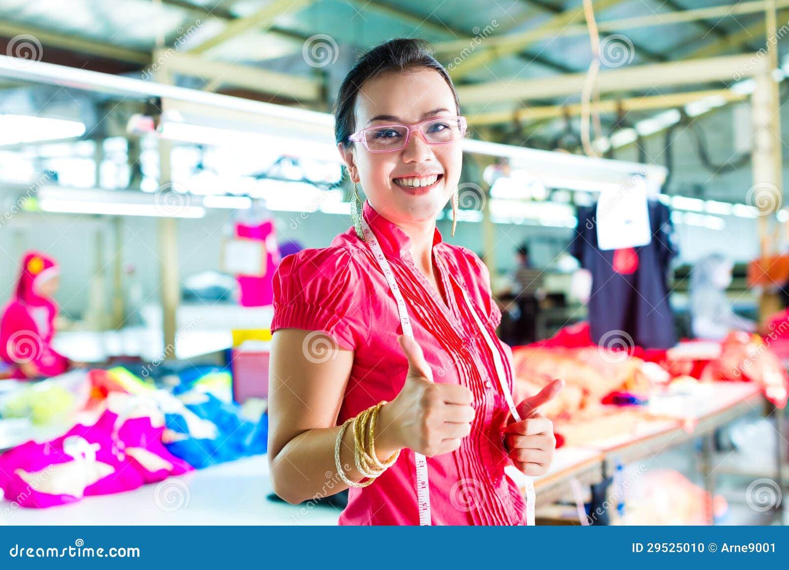 Costureira asiática em uma fábrica de matéria têxtil