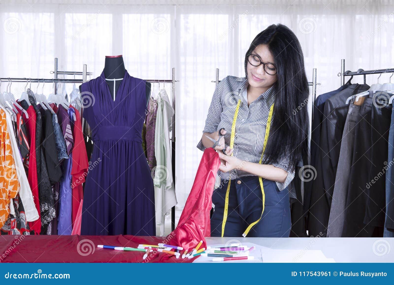 Costurera asiática que corta una tela en el lugar de trabajo
