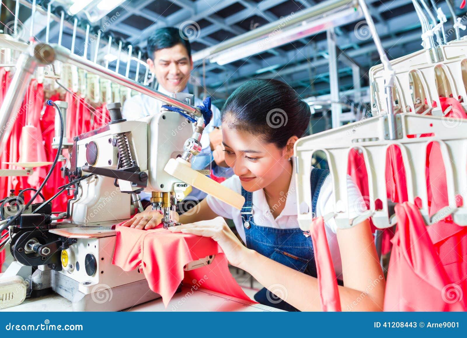 Costurera indonesia en fábrica asiática de la materia textil