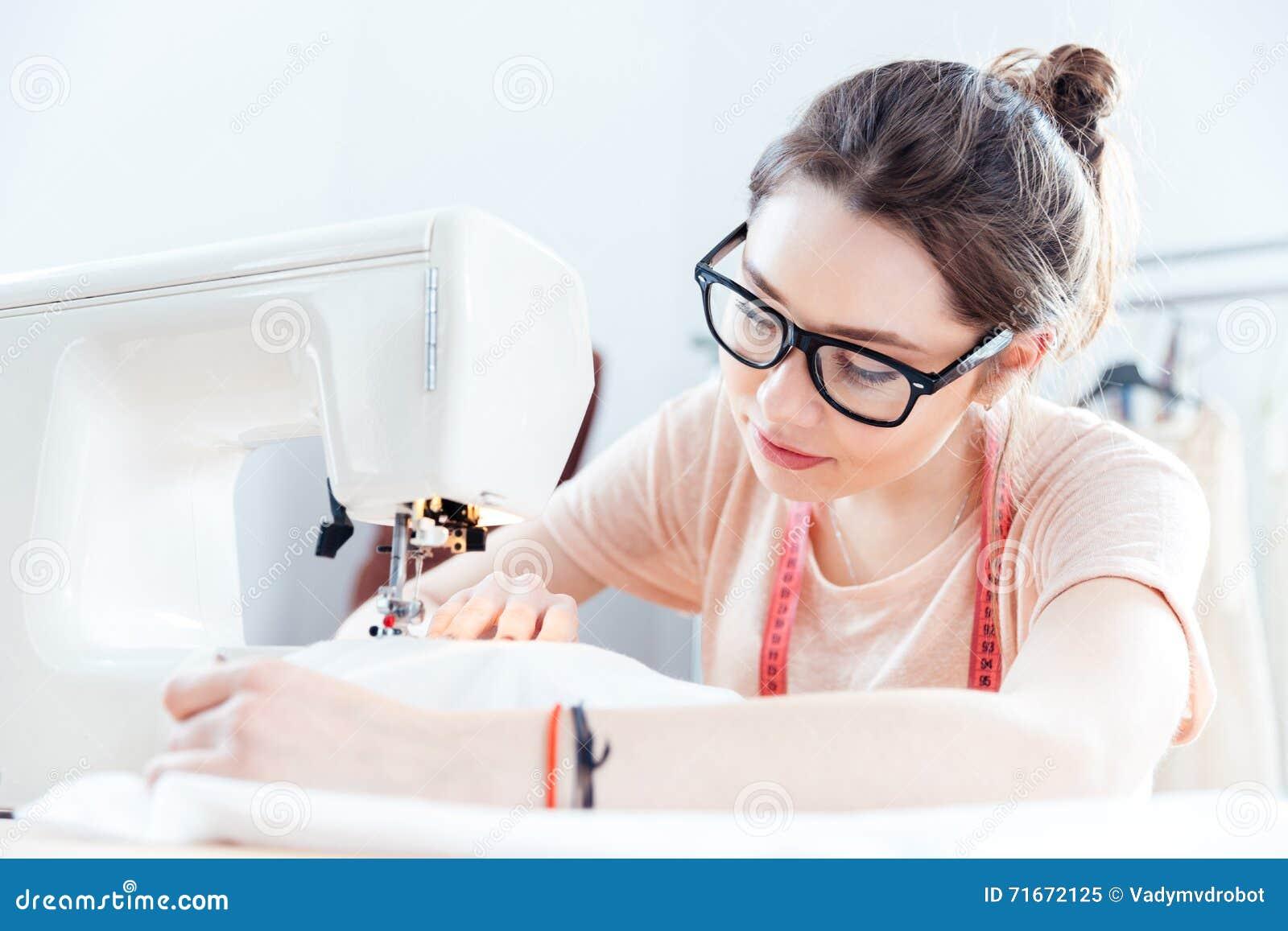 Costurera seria de la mujer en el trabajo con la tela del paño