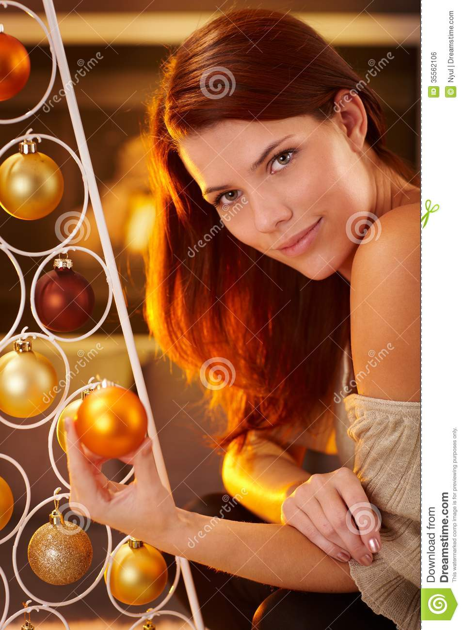 Cosy christmas portrait of smiling beauty by modern christmas tree