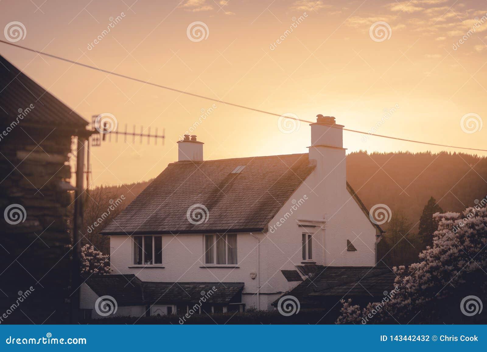 Cosy pokrywająca strzechą Angielska chałupa z ciepłym pomarańczowym słońca położeniem za nim po środku wiosny