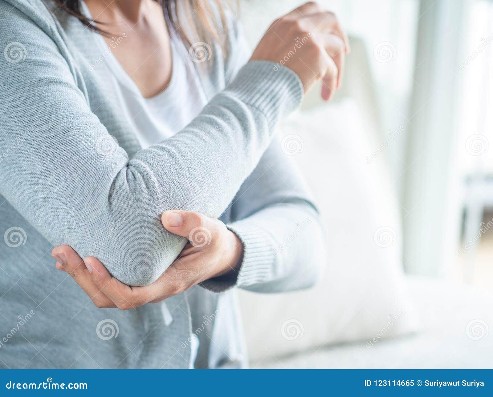 Cotovelo fêmea do ` s do close up Dor e ferimento do braço Cuidados médicos e MED