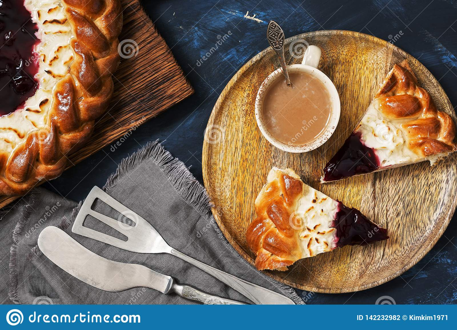 Cottage cheese cake with berry jam and coffee on a dark blue background. Top view, flat lying