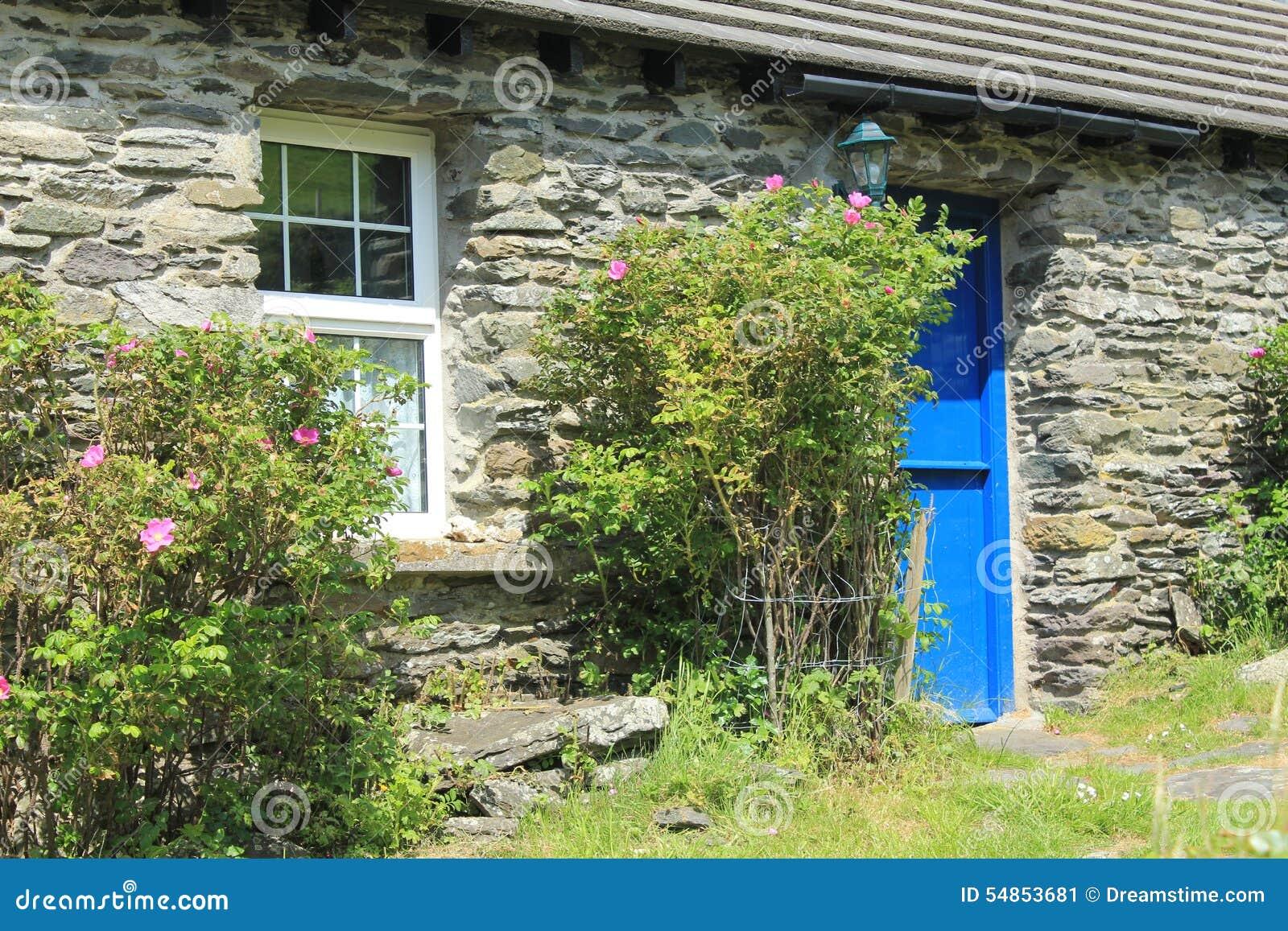 Cottage di pietra impilato con la porta blu in Irlanda