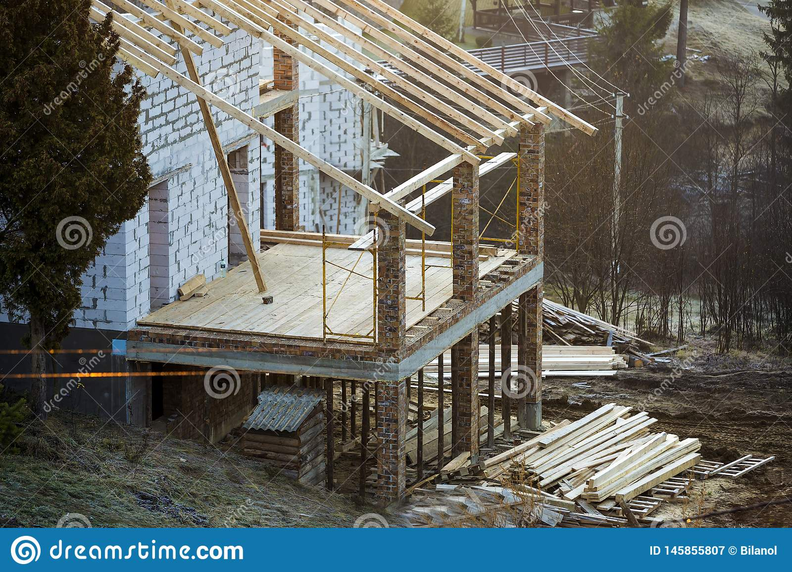 Cottage house building under construction with walls made of hollow foam insulation blocks, wooden roof frame and attached porch