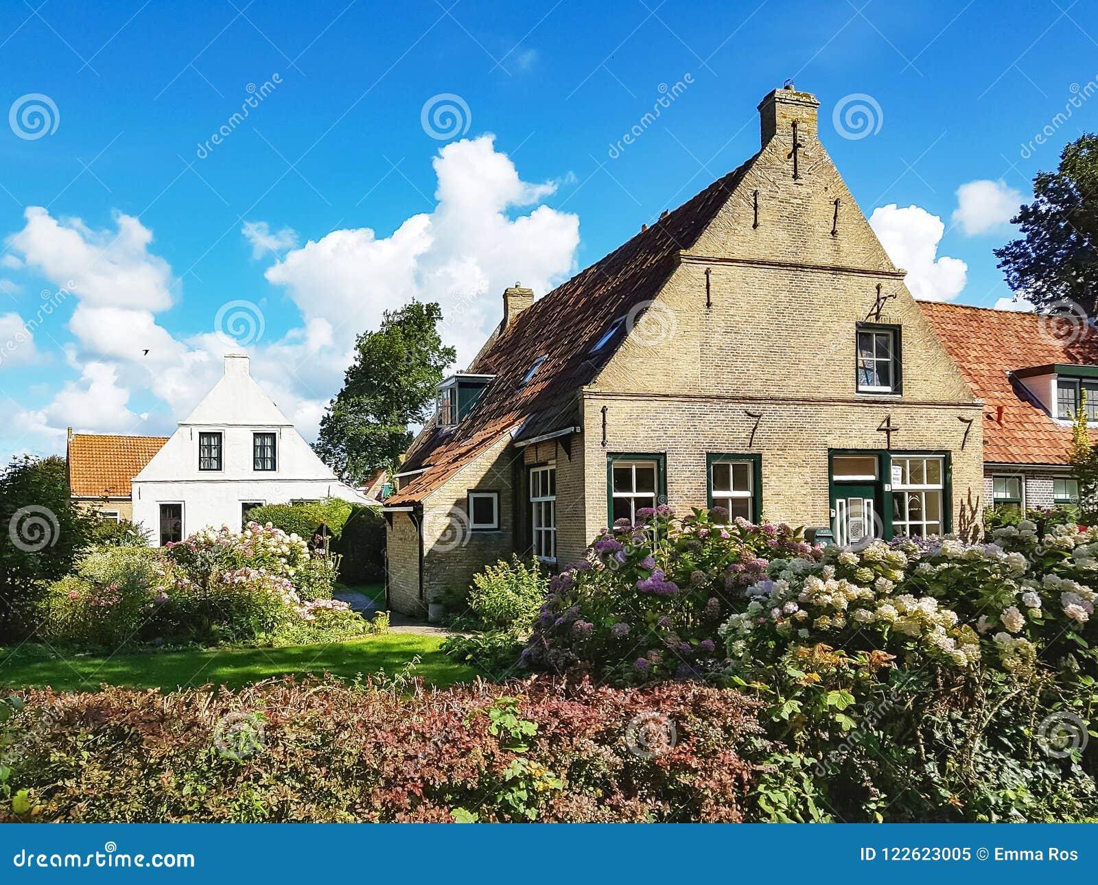 Cottage tipici sull isola Ameland sotto un cielo blu
